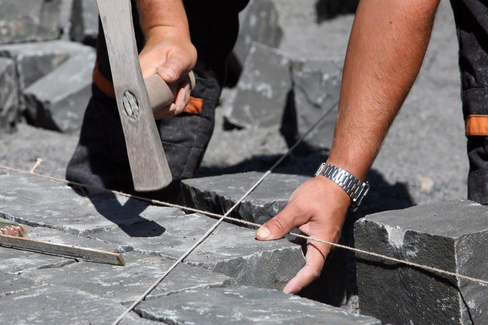 Detailaufnahme Handwerker beim Granit verlegen